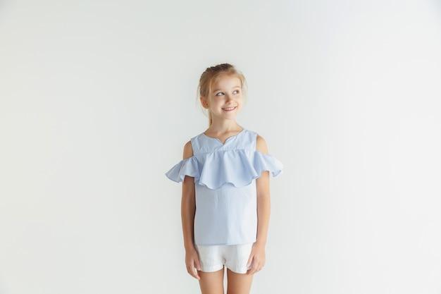 Élégante petite fille souriante posant dans des vêtements décontractés isolés sur fond de studio blanc. modèle féminin blonde caucasienne. émotions humaines, expression faciale, enfance. souriant, regardant de côté.
