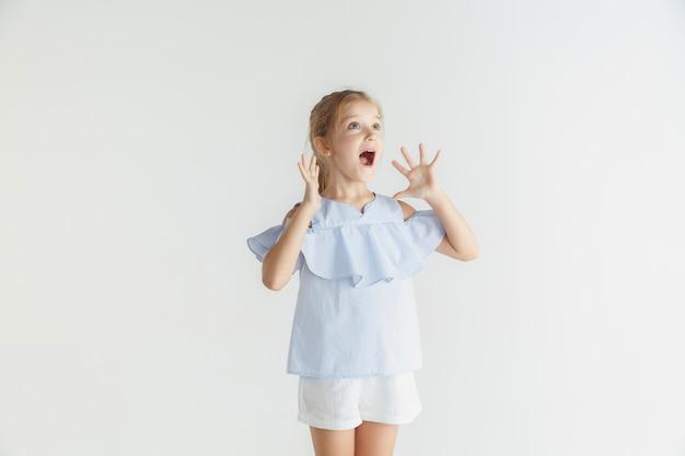 Élégante petite fille souriante posant dans des vêtements décontractés isolés sur fond de studio blanc. modèle féminin blonde caucasienne. émotions humaines, expression faciale, enfance, ventes. choqué, étonné.