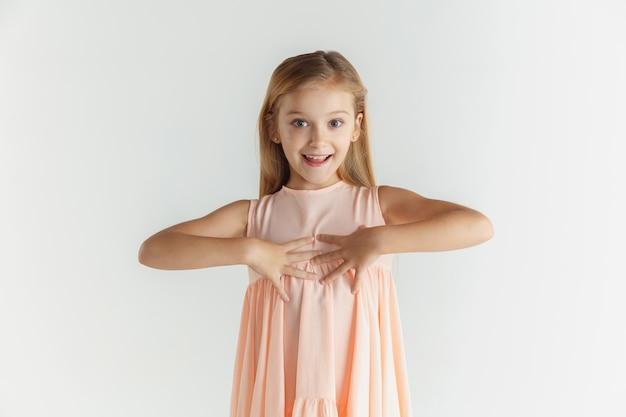 Élégante petite fille souriante qui pose en robe isolée sur fond de studio blanc. modèle féminin blonde caucasienne. émotions humaines, expression faciale, enfance. souriant, étonné, interrogé.