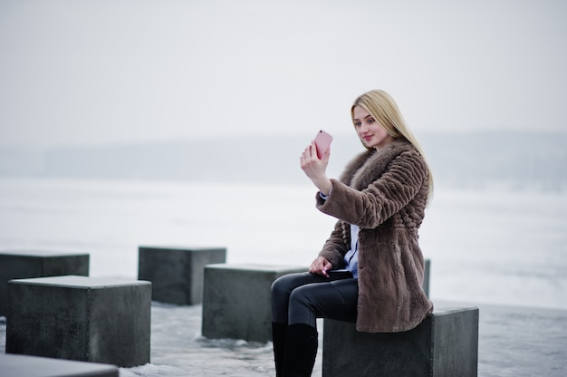 Élégante riche jeune femme blonde sur le manteau de fourrure à la recherche sur un smartphone rose sur la main, des cubes de pierre contre le lac gelé le jour de l'hiver.