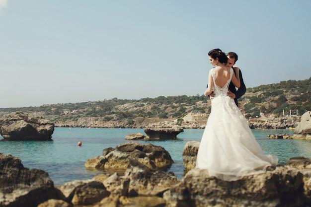 Élégante, souriante jeune mariée et mariée posant sur les rochers sur la plage