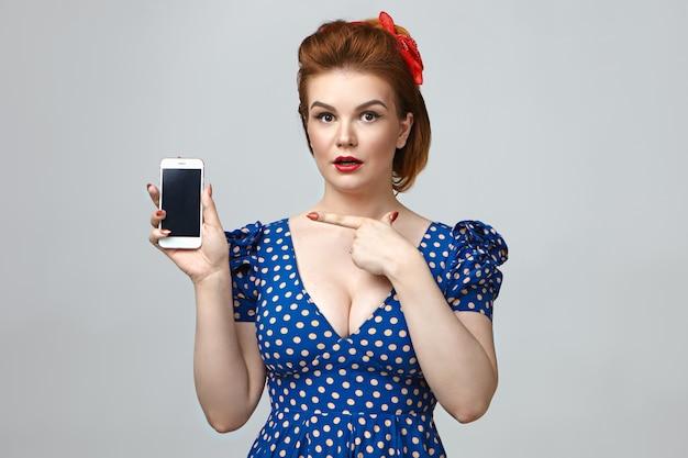 Élégante surprise jeune femme de race blanche en robe à pois découpée tenant le téléphone smrt, pointant le doigt sur l'écran de l'espace copie vierge