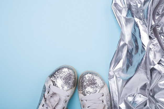 Élégantes chaussures femme printemps ou automne argent et manteau sur fond bleu.