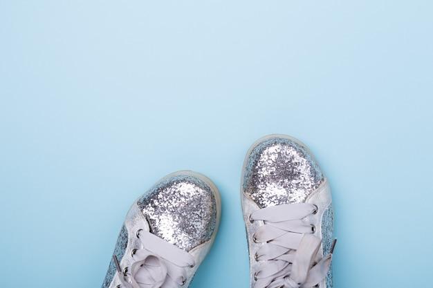 Élégantes chaussures femme printemps ou automne argentées sur fond bleu. concept de beauté et de mode. mise à plat, vue de dessus - image