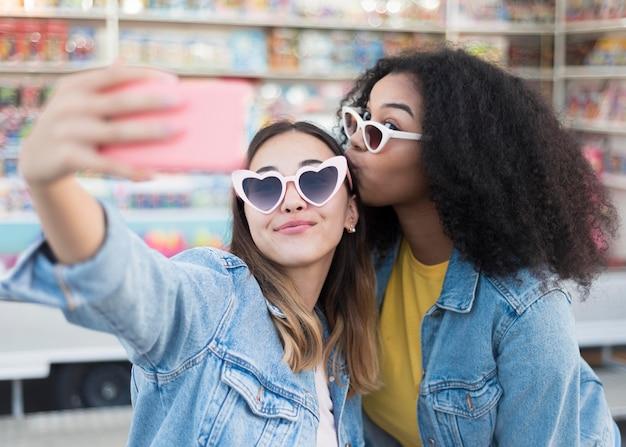 Élégantes jeunes filles prenant un selfie ensemble