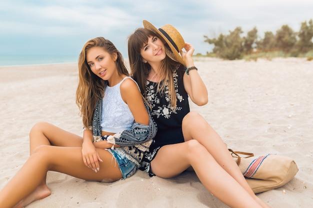 Élégantes jolies femmes en vacances d'été sur la plage, style bohème, amis ensemble, tendance de la mode, accessoires, souriant, émotion heureuse, humeur positive, expression du visage émotionnel, surpris, heureux