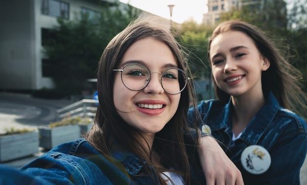 Élégants meilleurs amis heureux faisant selfie