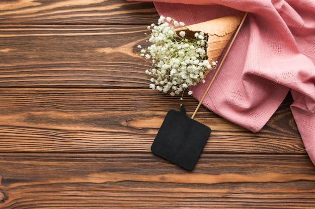 Élément de discours noir et gypsophile à l'intérieur du cornet de crème glacée sur un textile rose sur un fond texturé en bois