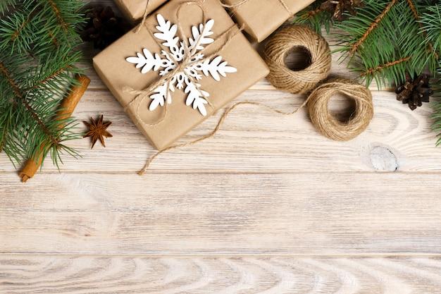 Éléments de décoration de noël: ficelle, branches d'arbre de noël avec cônes et plusieurs cadeaux décorés sur bois blanc