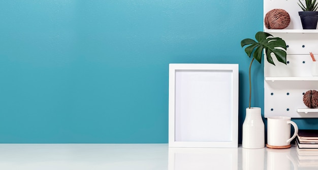 Éléments d'espace de travail créatif sur un bureau blanc avec cadre vide