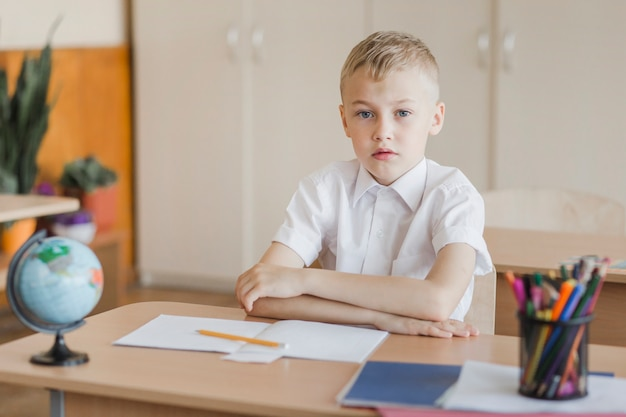 Élève assis avec les mains sur le bureau dans la salle de classe