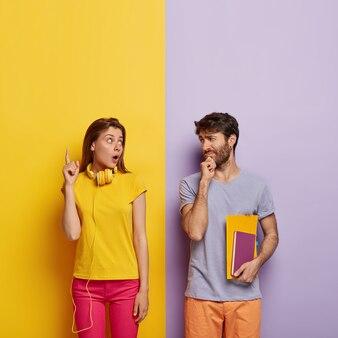 Un élève choqué montre quelque chose à un camarade de groupe, pointe vers le haut, l'homme à poils tient le menton et écoute attentivement, tient le bloc-notes