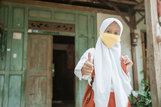 Élève du primaire asiatique indonésien portant un masque avant d'aller à l'école