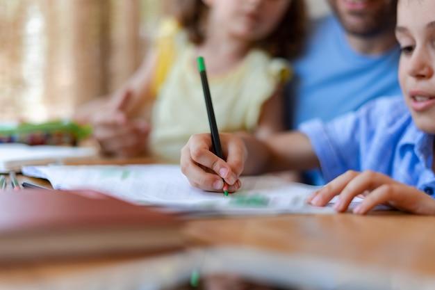 Un élève du primaire dessine aux crayons dans un cahier ou fait ses devoirs, sous la supervision étroite de sa sœur et de son père.