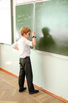 Élève du primaire écrit maths répondre au tableau
