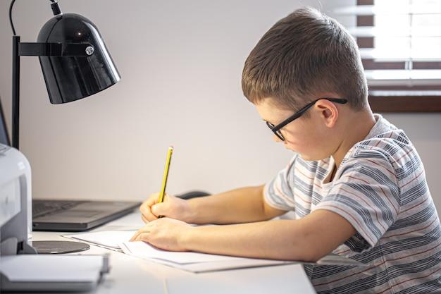 Un élève du primaire fait ses devoirs tout seul.