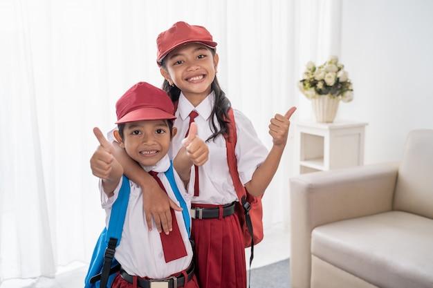 Élève du primaire portant l'uniforme scolaire montrant les pouces vers le haut