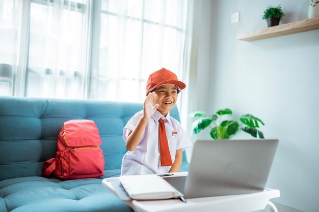 Élève du primaire en uniforme saluant son professeur et son ami lors d'une session de cours en ligne