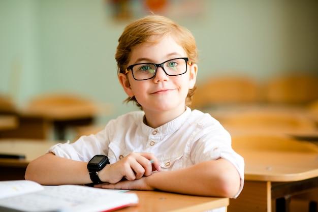 Élève de l'école blonde mignonne avec des lunettes élégantes écrit en classe