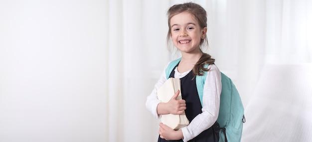 Élève de l'école élémentaire fille avec un sac à dos et un livre