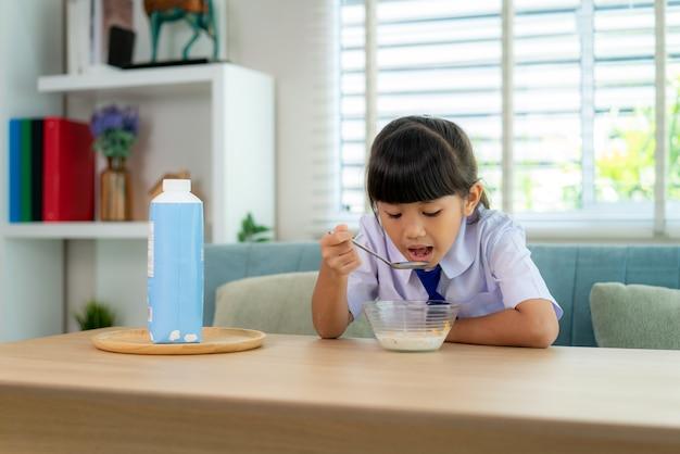 Élève de l'école élémentaire fille en uniforme de manger des céréales pour le petit déjeuner avec du lait le matin