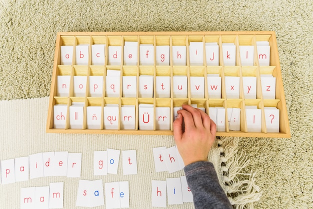 Un élève d'une école montessori utilisant des cartes avec des lettres pour composer des mots et des phrases sur un tapis.