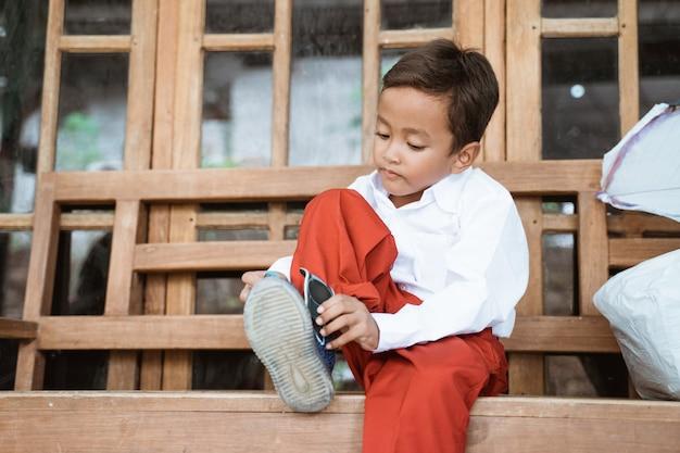 Élève de l'école primaire indonésienne se prépare à l'école le matin, attachant des chaussures devant la maison