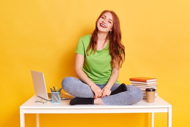 Élève éduquant assis sur une table avec les jambes croisées