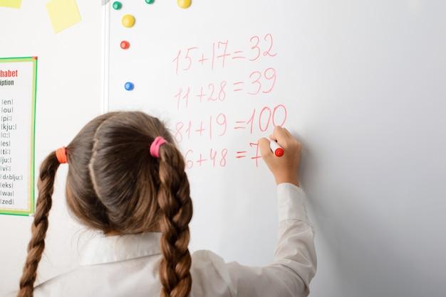 Élève européen d'école primaire écrit sur tableau blanc