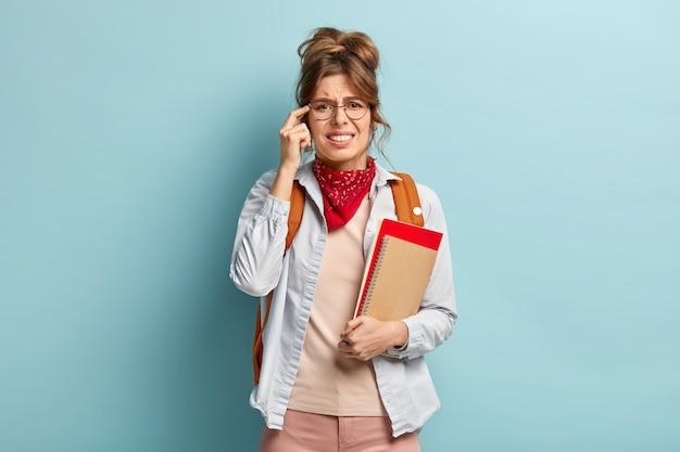 Un élève fatigué insatisfait garde le doigt sur la tempe, a mal à la tête après de longues études, tient un journal et un manuel