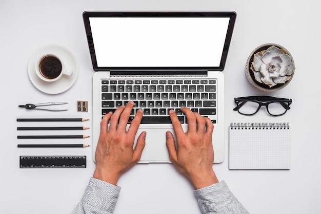 Elevé de la main d'une personne travaillant sur un ordinateur portable au bureau