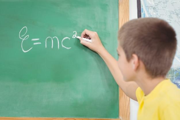 Élève mignon écrit sur le tableau dans une salle de classe