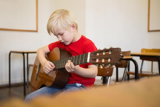 Élève mignon jouant de la guitare dans la salle de classe