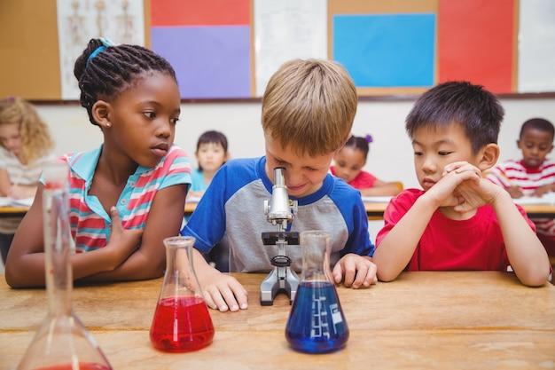Élève mignon regardant à travers le microscope