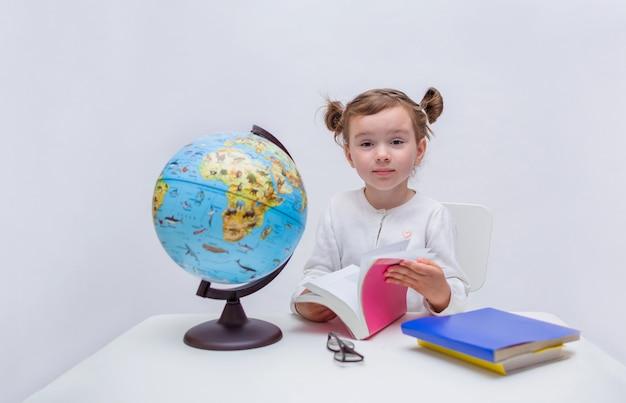 Élève de petite fille est assise à une table avec un livre et un globe sur un blanc isolé