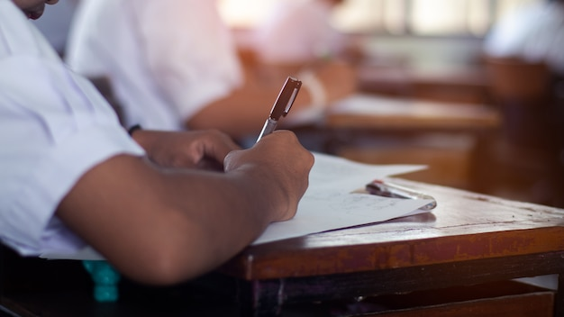 Élève prend un examen et écrit la réponse en salle de classe pour le concept de test de l'éducation.