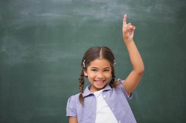 Élève souriant, levant sa main