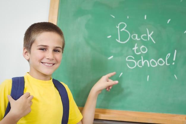 Élève souriant pointant sur le dos à l'école signe sur tableau noir