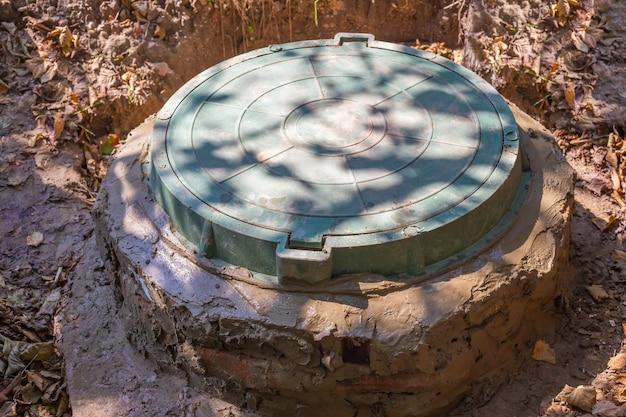 Élever l'embouchure d'un puits en brique. installation d'une fosse septique pour une maison.