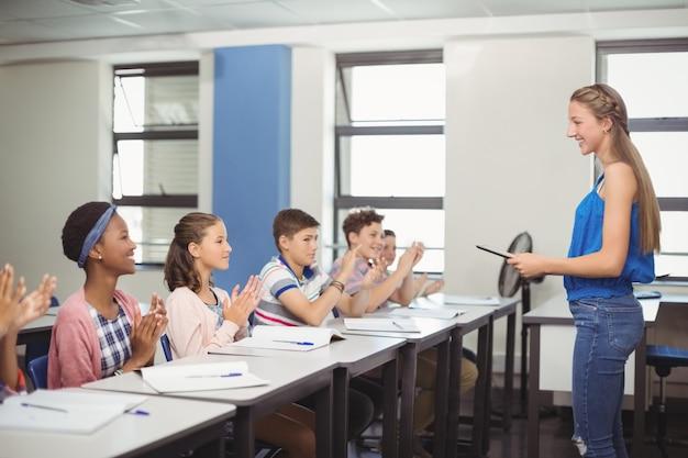 Les élèves appréciant camarade de classe après la présentation en classe