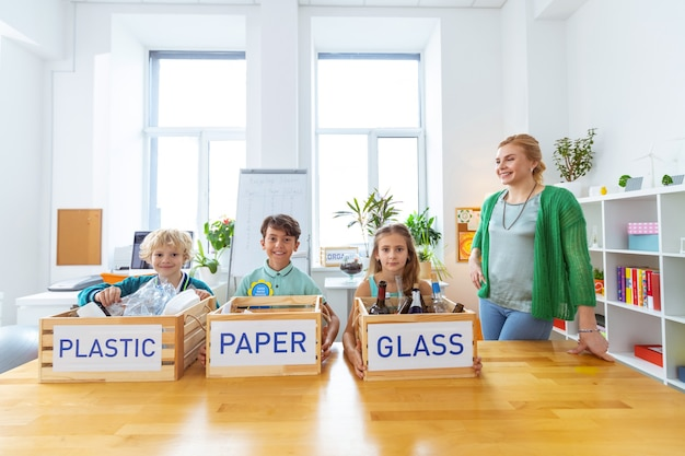 Élèves assidus. enseignant satisfait après avoir trié les déchets avec des élèves diligents à la leçon d'écologie