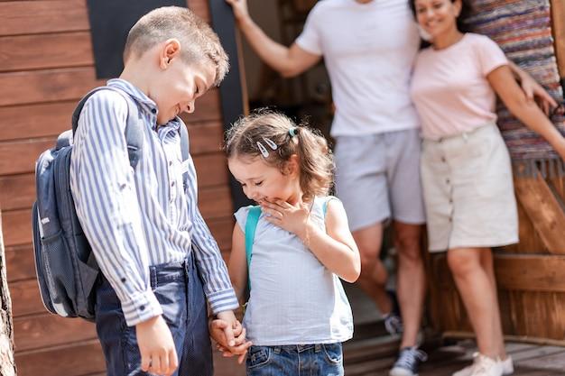 Les élèves du primaire se réjouissent de la nouvelle journée d'école, se tenant la main en riant et en allant à l'école pendant que leurs parents attentionnés les regardent.