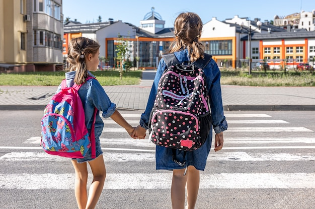 Les élèves du primaire vont à l'école en se tenant la main le premier jour d'école retour à l'école