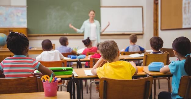 Élèves écoutant leur professeur au tableau