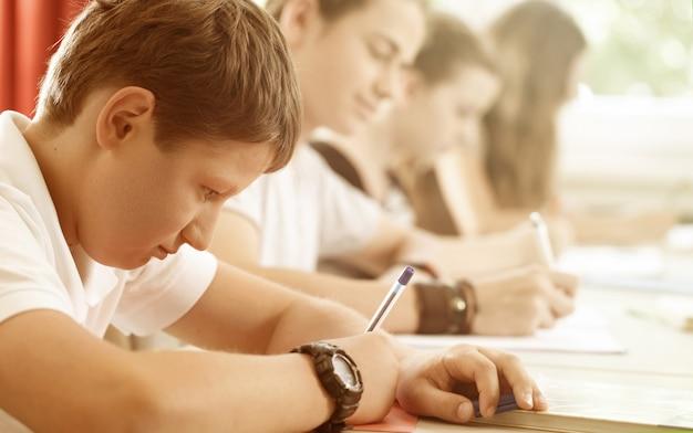 Les élèves ou les élèves écrivent le test à l'école étant concentré