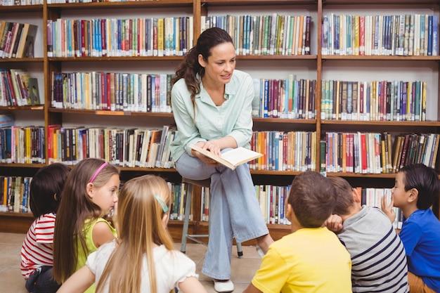 Élèves et enseignant dans la bibliothèque en utilisant un ordinateur