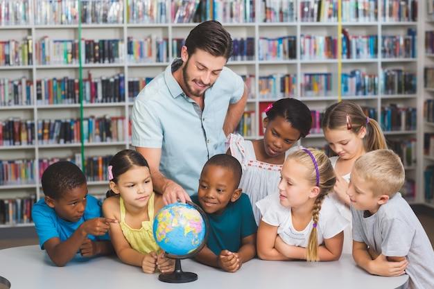 Élèves Et Enseignants à La Recherche D'un Globe Dans La Bibliothèque Photo Premium