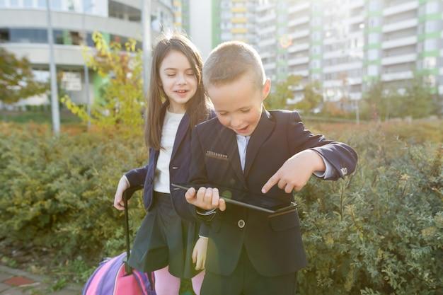 Élèves garçon et fille à l'école primaire avec tablette numérique