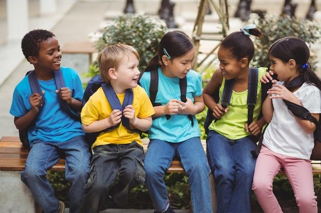 Élèves heureux avec des cartables assis sur un banc