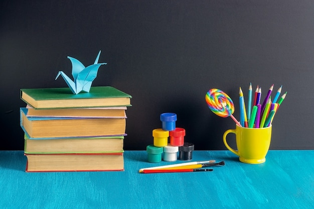 Elèves sur le lieu de travail. livres, papeterie, peinture, gouache et grue en origami sur table bleue